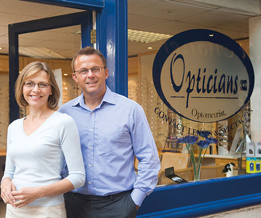 A photo of a male and a female optician stood in their practice doorway.